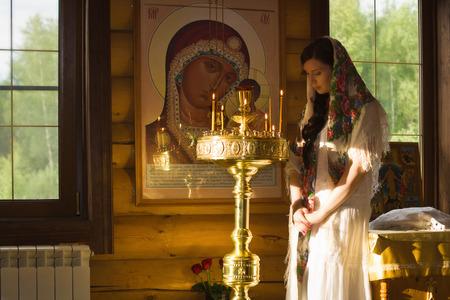 Russische vrouw met kaarsen in de Russisch-orthodoxe Kerk Stockfoto