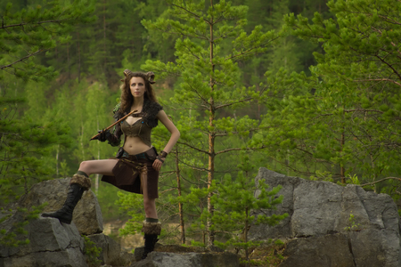 faun: Pretty female faun in a wood. Woman with a mythological creature playing flute
