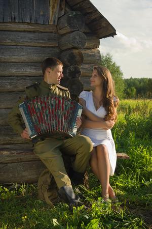 wojenne: Radziecki żołnierz w mundurze II wojny światowej gry na akordeonie dziewczyna. Szczęśliwa para.
