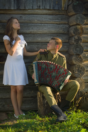 Soviet soldier in uniform of World War II playing accordion to girl. Happy couple.