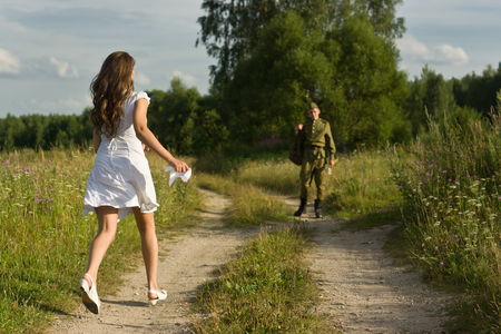 russian girl: Happy girl meets a soldier. Return of the Soviet soldier in uniform of World War II home