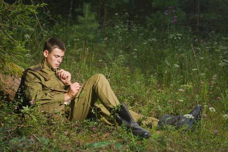 reenacting: Soviet soldier in uniform of World War II writes a letter Stock Photo