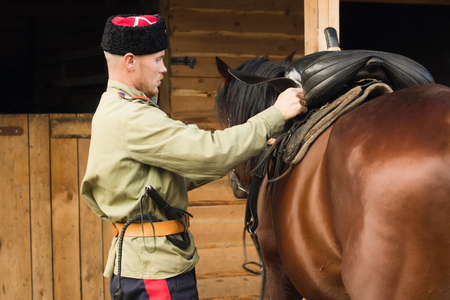 Russian Cossack grooming horse in the stall