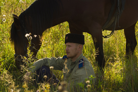 drover: Russian Cossack and a horse resting in the summer field Stock Photo
