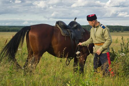 summer field: Russian Cossack and a horse resting in the summer field Stock Photo