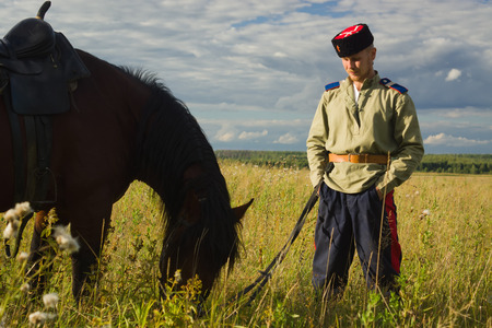archival: Russian Cossack and a horse resting in the summer field Stock Photo
