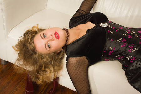 Crime scene simulation. Strangled woman lying on sofa