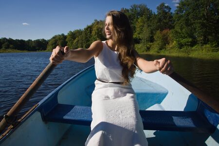 impressive: Young Girl rowing oars in the boat Stock Photo