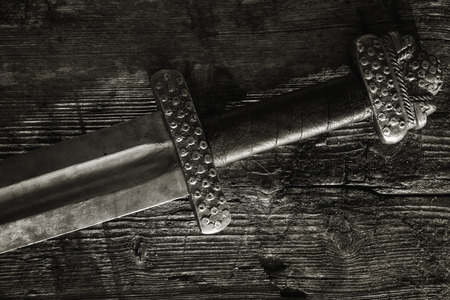War symbol. Medieval viking sword against a wooden wall Stock fotó