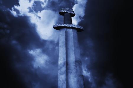 medieval: Símbolo de la Guerra. Espada medieval vikingo contra un cielo dramático Foto de archivo