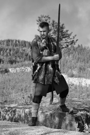 vikingo: Vikingo atacar con una espada en las montañas