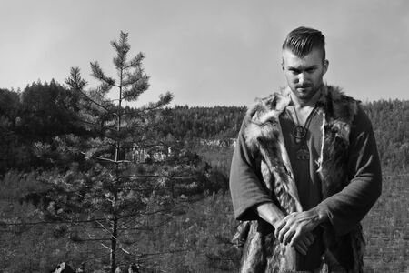 masculinity: Male dressed in Barbarian style with sword in the mountains