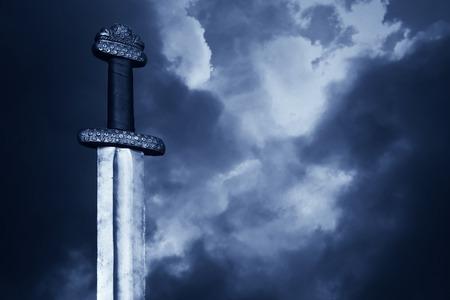 戦争のシンボル。劇的な空戦中世のバイキングの剣 写真素材