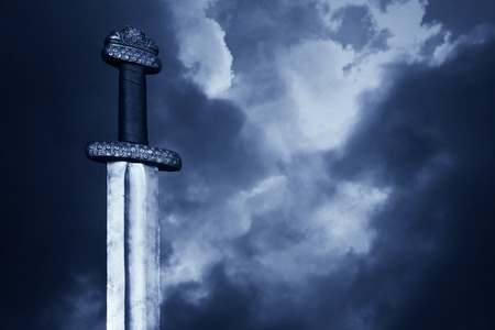 espadas medievales: S�mbolo de la Guerra. Espada medieval vikingo contra un cielo dram�tico Foto de archivo