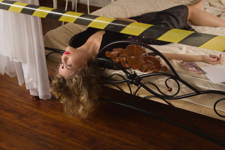 Crime scene simulation. Lifeless woman lying on a bed