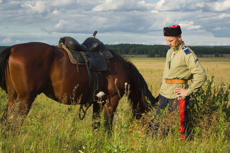 reproduction: Russian Cossack and a horse resting in the summer field Stock Photo