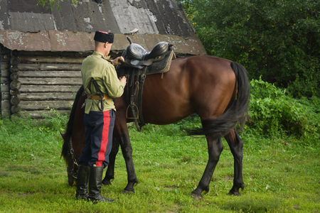 steppe: Russian Cossack and a horse resting in the summer field Stock Photo