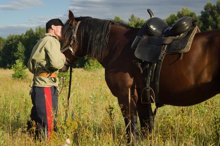 cavalryman: Cosaco ruso y un caballo descansando en el campo de verano