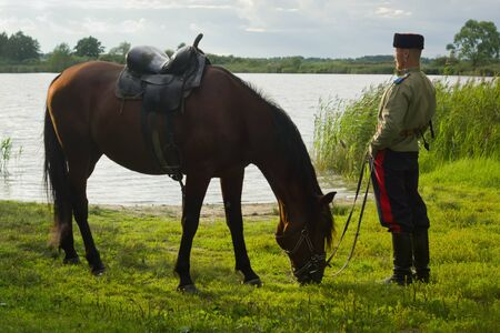 steppe: Russian Cossack and a horse resting on the lake