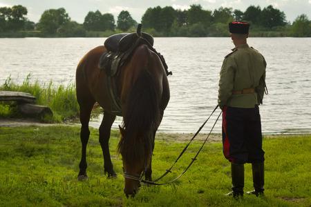 cavalryman: Cosaco ruso y un caballo descansando sobre el lago
