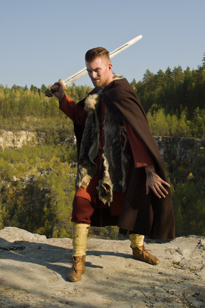 Viking attacking with a sword in the mountains Stock Photo