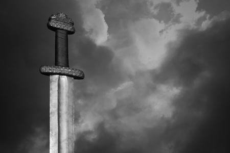 fantasy sword: War symbol. Medieval viking sword against a dramatic sky