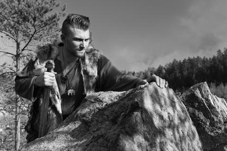 vikingo: Vikingo con la espada en un acantilado en las montañas