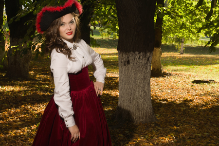 Pretty woman dressed in a retro-style on the autumn alley Stock Photo