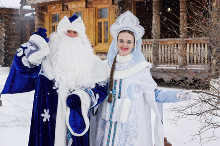 ded moroz: Russian Christmas characters: Ded Moroz (Father Frost) and Snegurochka (Snow Maiden) with gifts bag near a russian home Stock Photo