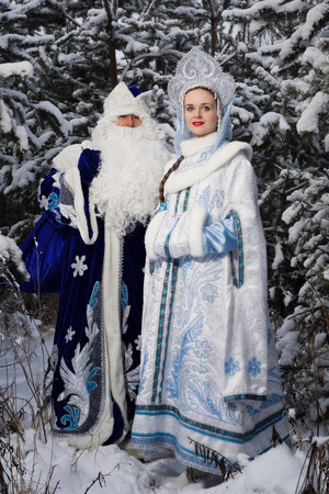 snegurochka: Russian Christmas characters: Ded Moroz (Father Frost) and Snegurochka (Snow Maiden) with gifts bag in the winter forest