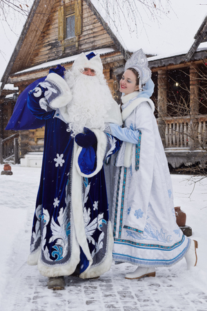 Russian Christmas characters: Ded Moroz (Father Frost) and Snegurochka (Snow Maiden) with gifts bag near a russian home Stock Photo