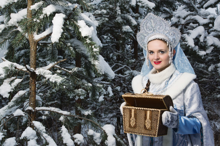 Russian Christmas characters: Snegurochka (Snow Maiden) with gifts bag in the winter forest