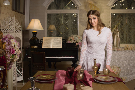 soloist: Pretty woman in evening dress posing in a vintage interior with a piano Stock Photo