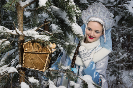 snegurochka: Russian Christmas characters: Snegurochka (Snow Maiden) with gifts bag in the winter forest