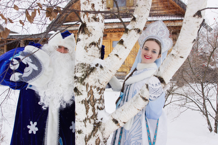 snegurochka: Russian Christmas characters: Ded Moroz (Father Frost) and Snegurochka (Snow Maiden) with gifts bag near a russian home Stock Photo