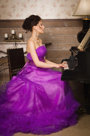 instrumentalist: Pretty woman dressed in long lace dress playing piano