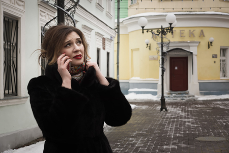 rendezvous: A woman in a fur coat on a city street. Unsuccessful rendezvous. He did not come. Stock Photo