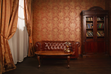 Classical library room with leather armchair, wooden table and bookcase Stockfoto