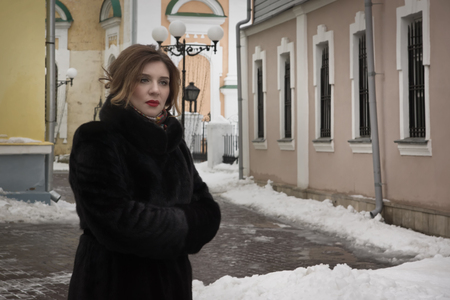 come in: A woman in a fur coat on a city street. Unsuccessful rendezvous. He did not come. Stock Photo