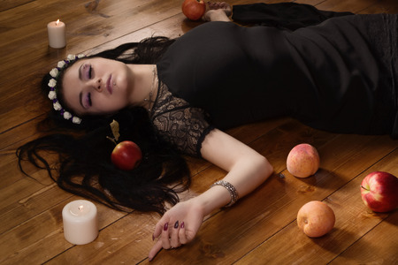 poisoned: Gothic Snow White. Woman with poisoned apple lies on the floor Stock Photo