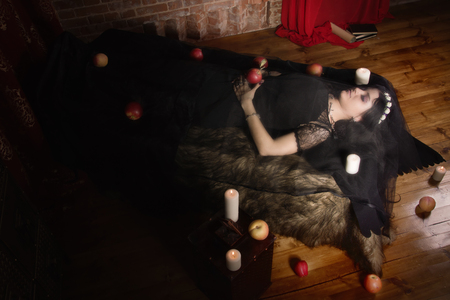 witchery: Gothic Snow White. Woman with poisoned apple lies in a tomb