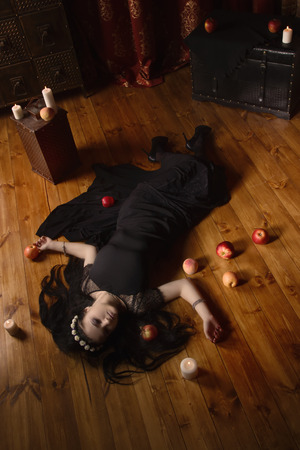 witchery: Gothic Snow White. Woman with poisoned apple lies on the floor Stock Photo