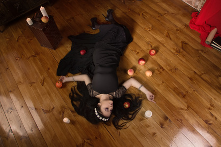 Gothic Snow White. Woman with poisoned apple lies on the floor Stock Photo