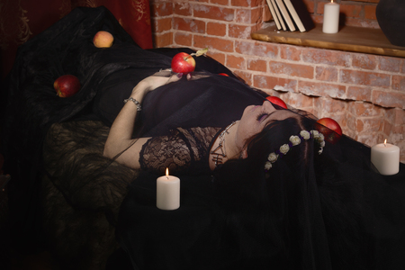 Gothic Snow White. Woman with poisoned apple lies in a tomb