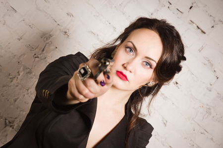 homicide: Noir film style woman in a black suit posing with a gun