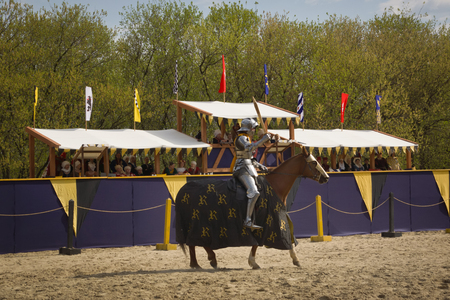 chivalry: The horse knight in an armour and in a helmet with a sword in a hand. St.George knightly tournament. Moscow on May 1, 2016