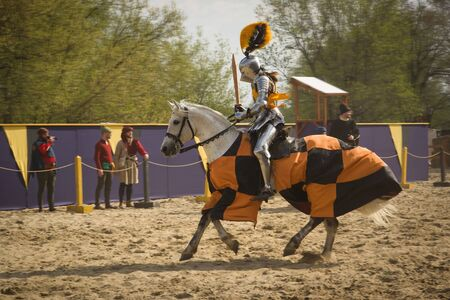 showmanship: The horse knights in an armour and in a helmet with a sword in a hand. St.George knightly tournament. Moscow on May 1, 2016