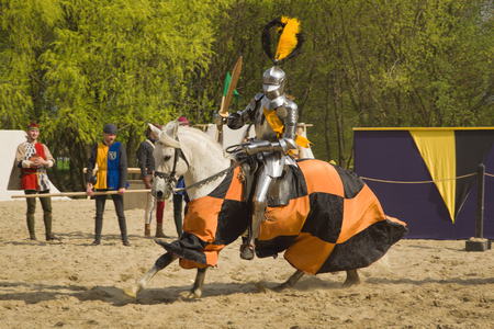 knightly: The horse knights in an armour and in a helmet with a sword in a hand. St.George knightly tournament. Moscow on May 1, 2016