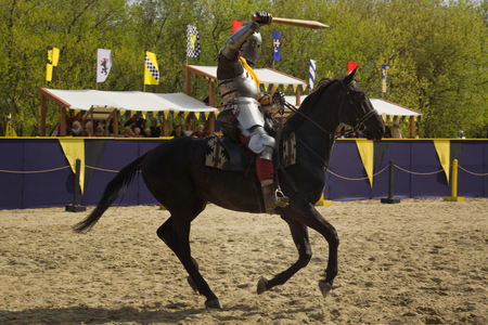 showmanship: The horse knight in an armour and in a helmet with a sword in a hand. St.George knightly tournament. Moscow on May 1, 2016