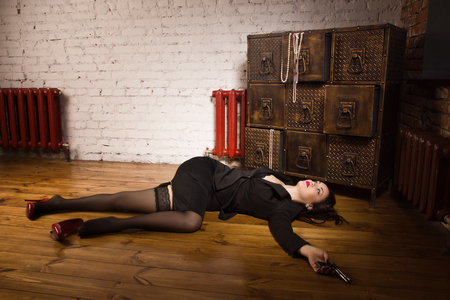 coroner: Detective scene imitation. Woman in a black suit with gun lying on the floor Stock Photo